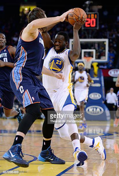 Draymond Green of the Golden State Warriors drives on Josh McRoberts of the Charlotte Bobcats at ORACLE Arena on February 4 2014 in Oakland...