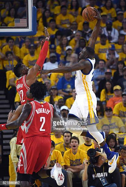 Draymond Green of the Golden State Warriors goes up to shoot and score over Dwight Howard of the Houston Rockets in the first quarter in Game One of...