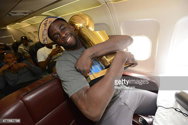 Draymond Green of the Golden State Warriors holds the NBA trophy on the plane as the team travels home from Cleveland after winning the 2015 NBA...