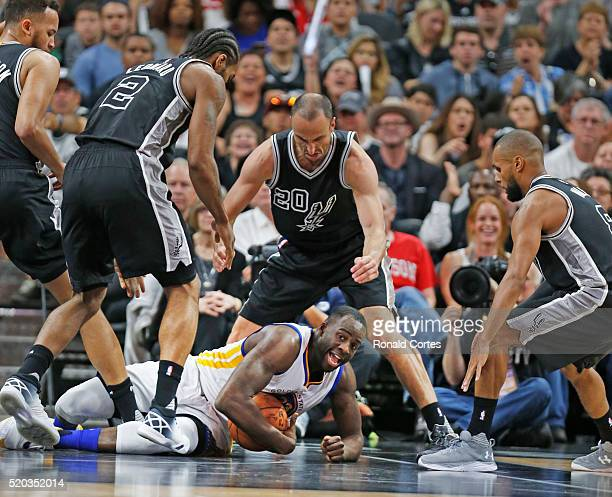 Draymond Green of the Golden State Warriors is surrounded by San Antonio Spurs players at ATT Center on April 10 2016 in San Antonio Texas The...