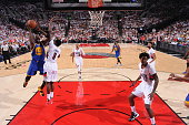 Draymond Green of the Golden State Warriors shoots against AlFarouq Aminu of the Portland Trail Blazers in Game Three of the Western Conference...