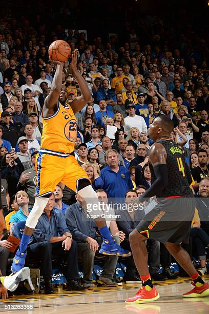 Draymond Green of the Golden State Warriors shoots for three against Paul Millsap of the Atlanta Hawks on March 1 2016 at Oracle Arena in Oakland...