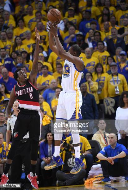 Draymond Green of the Golden State Warriors shoots over AlFarouq Aminu of the Portland Trail Blazers in the fourth quarter during Game One of the...