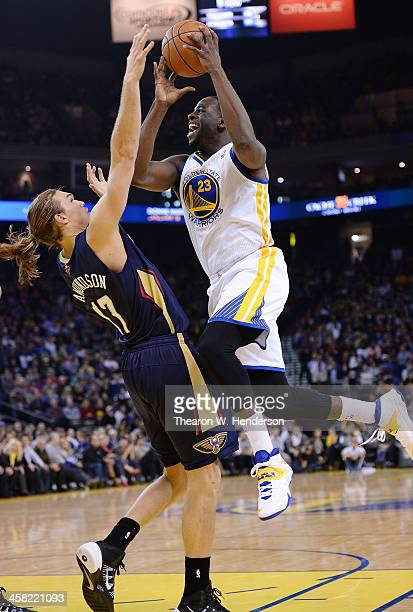 Draymond Green of the Golden State Warriors shoots over Lou Amundson of the New Orleans Pelicans at ORACLE Arena on December 17 2013 in Oakland...