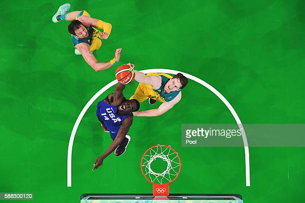 Draymond Green of United States grabs the rebound against Cameron Bairstow and David Andersen of Australia during the Men's Preliminary Round Group A...