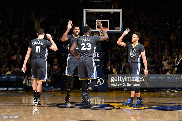 Draymond Green Stephen Curry Kevin Durant and Klay Thompson of the Golden State Warriors high five each other during the game against the Portland...