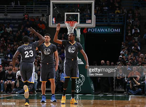 Draymond Green Zaza Pachulia and Kevin Durant of the Golden State Warriors celebrate during a game against the Milwaukee Bucks on November 19 2016 at...