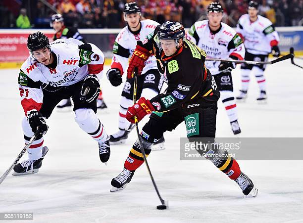 Drayson Bowman of Duesseldorfer EG takes a shot under the pressure of Pascal Zerressen of Koelner Haie during the Ice Hockey DEL match between...