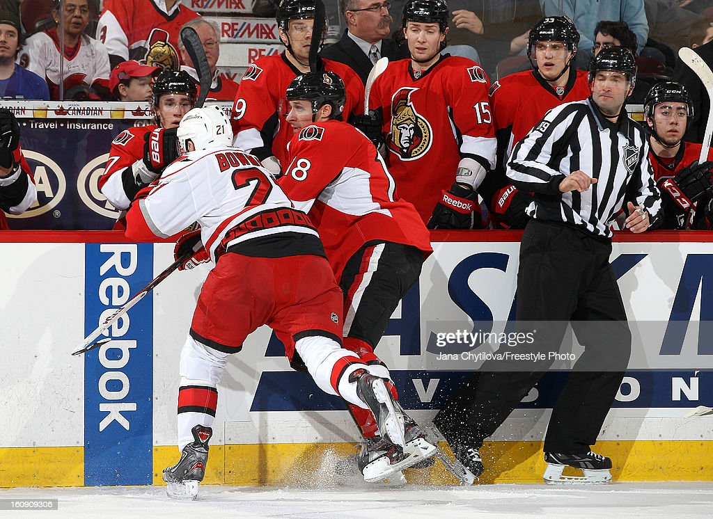 <a gi-track='captionPersonalityLinkClicked' href=/galleries/search?phrase=Drayson+Bowman&family=editorial&specificpeople=4111563 ng-click='$event.stopPropagation()'>Drayson Bowman</a> #21 of the Carolina Hurricanes checks Jim O'Brien #18 of the Ottawa Senators against the boards as linesman Steve Miller #89 reacts, during an NHL game at Scotiabank Place on February 7, 2013 in Ottawa, Ontario, Canada.
