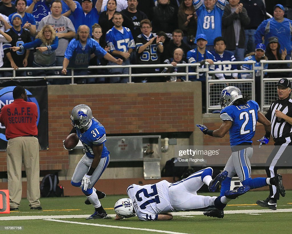 Drayton Florence #31 runs back an interception for a touchdown. The touchdown was not allowed because of a penalty on teammate Jacob Lacey #21 for pushing from behind on Andrew Luck #12 of the Indianapolis Colts at Ford Field on December 2, 2012 in Detroit, Michigan.