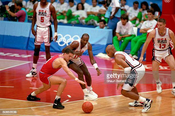 Drazen Petrovic of Croatia goes after the ball against Charles Barkley and Clyde Drexler of the United States in the 1992 Olympic game on August 8...