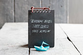 Dream big, set goals, take action on blackboard written, and a paper boat on an old table