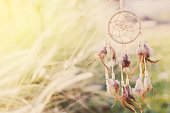 Close up of Dream Catcher on meadow background with soft vintage tone