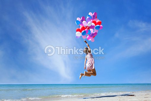 dream concept, girl flying with multicolored balloons, jump : Foto de stock