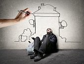 Homeless man is sitting on the ground while  hand is drawing a house on the wall