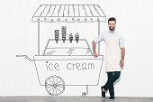 Handsome young man in apron standing in front of the wall and leaning at the pencil drawn ice cream cart