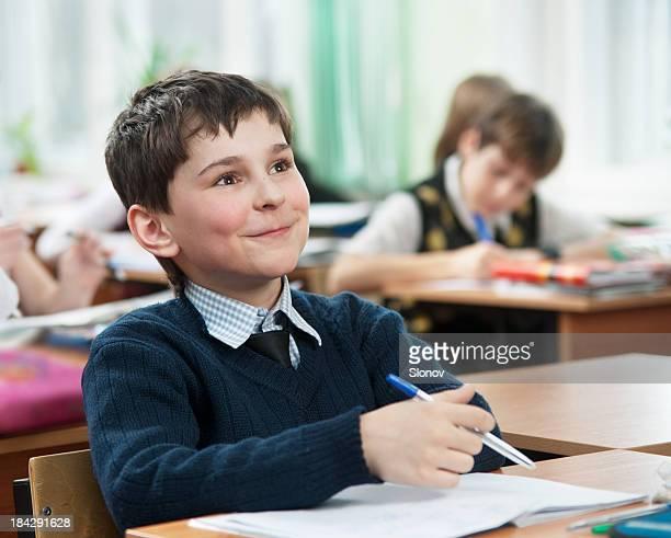 Dreaming schoolboy at classroom