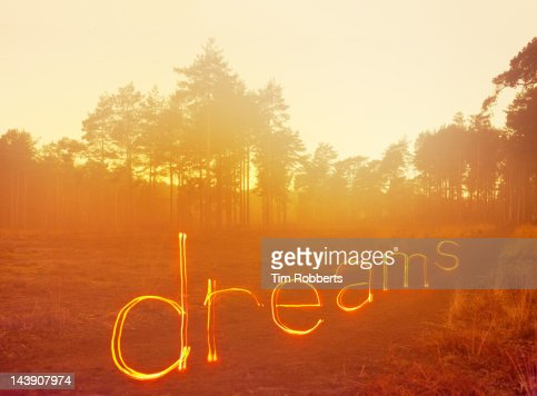'dreams' written in light on misty heath. : Foto de stock