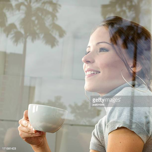 Dreamy and happy young woman with coffee cup