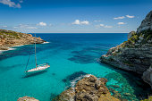 Dream bay seascape with turquoise transparent water and sailing boat. Mallorca island, Spain