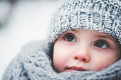 dreamy cozy outdoor portrait of toddler child girl in winter, wearing grey knitted hat and scarf