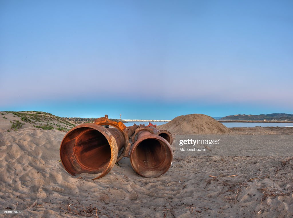 Dredge pipes lying on the beach ready for assembly. : Stock Photo