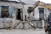 A dreedger takes down what is left of a column of a house that was damaged from Hurricane Ike in the El Cerro district September 9 2008 in Havana...