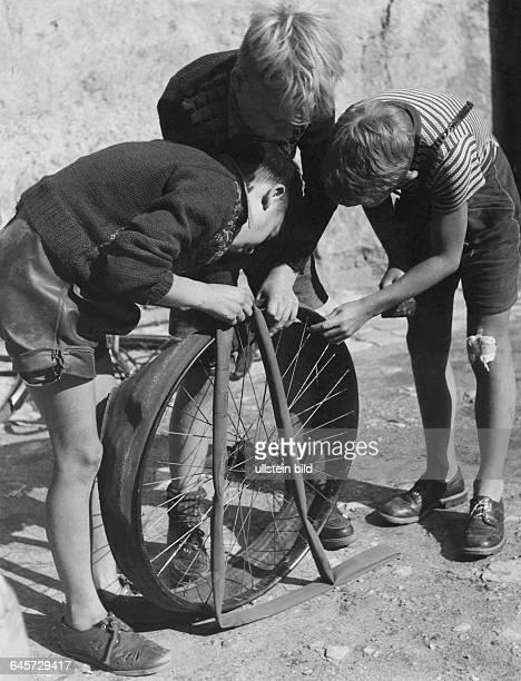Drei Freunde ziehen neuen Fahrradschlauch ein 50er Jahre