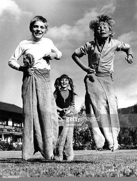 Drei Kinder beim Sackhüpfen 70er Jahre