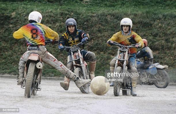 Drei Spieler gegnerischer Mannschaften auf ihren Motorrädern während der MotoballEuropameisterschaft 1994 in Baden Der Spielball liegt zwischen ihnen...