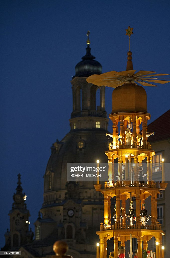Dresden's landmark the Church of Our Lady (Frauenkirche, L) can be seen behind a christmas pyramid at the Striezelmarkt, Christmas market just after its opening on November 28, 2012 in Dresden, eastern Germany. Visitors of the Christmas market can buy the traditional Striezel or Stollen fruit loaf, hot punch, gingerbread and craftwork at around 240 market stands up to Christmas Eve. Striezel (or Stollen), a fruit loaf made of yeast dough, almonds, raisins and other ingredients, is a culinary specialty of the eastern German town. MICHAEL