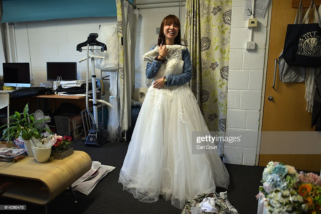 Dress assistant Susan Su holds a wedding dress as preparations are made for Charles Qian and his fiance Echo Li, both from Shenzhen in China, to have pre-wedding photographs taken next to London landmarks, on October 11, 2016 in London, England. It's a Chinese custom for couples to have their wedding photos taken before they are married and on the wedding day the photos will be shown to guests on cards and big screens. Photography studios such as J.R Studios in east London have seen business boom as the capital has become increasingly popular as a location for pre-wedding photography thanks in part to its instantly recognisable landmarks.