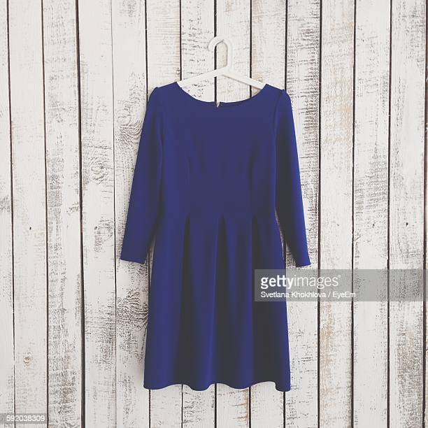 Dress Hanging Against Wooden Wall