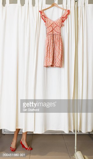 Dress hanging outside dressing room, woman changing inside room