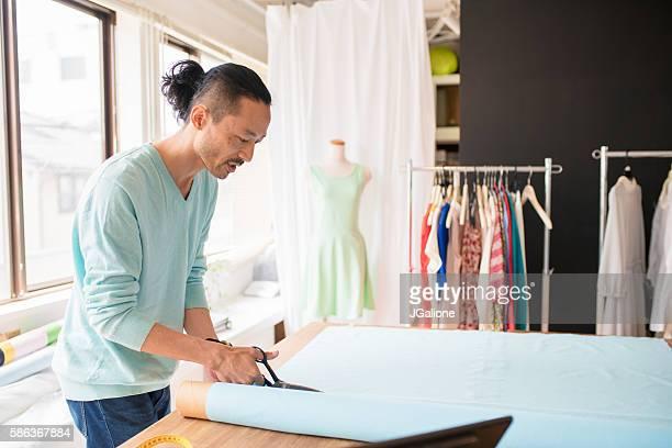 Dress maker cutting fabric