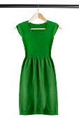 Green knitted dress on clothes rack isolated over white