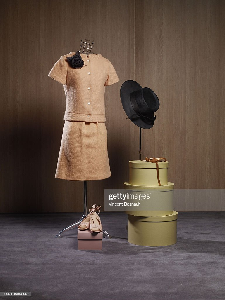 Dress on dressmaker's model by hat boxes and shoes