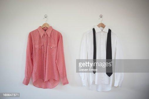 Dress shirt with tie hanging next to cowboy shirt