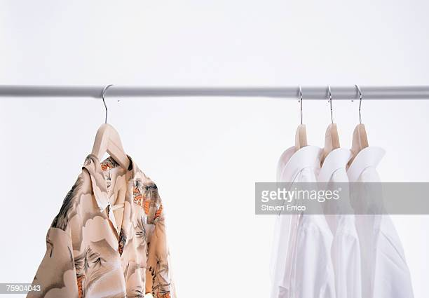 Dress shirts hanging next to Hawaiian shirt