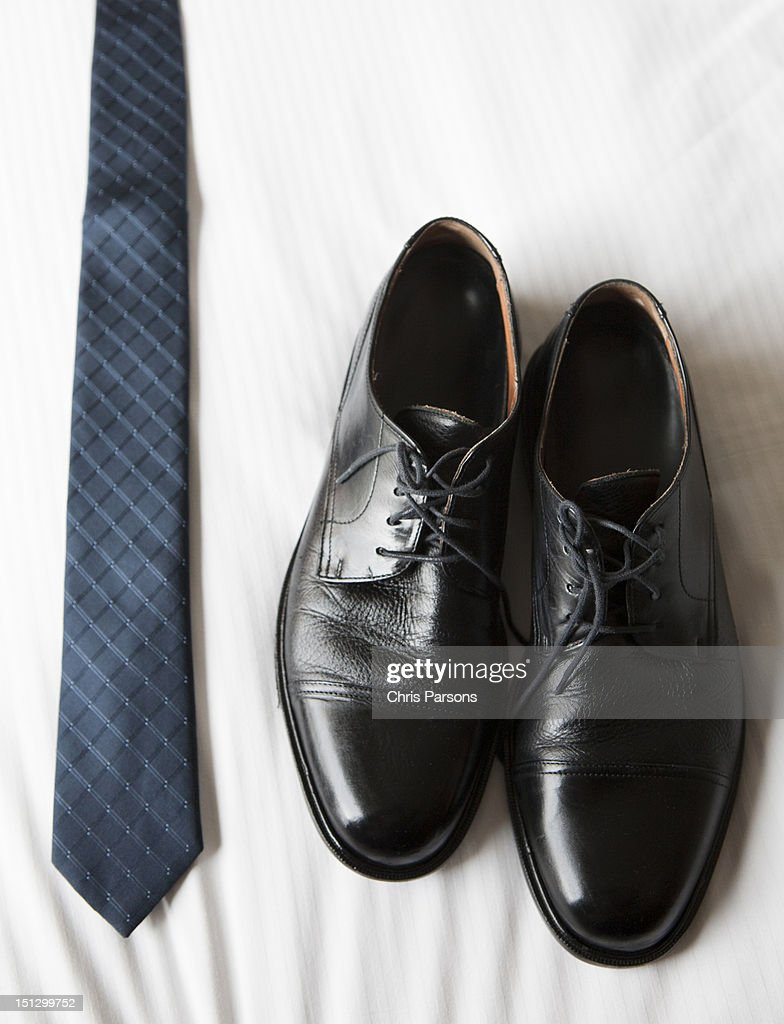 Dress shoes and tie laid out on a bed