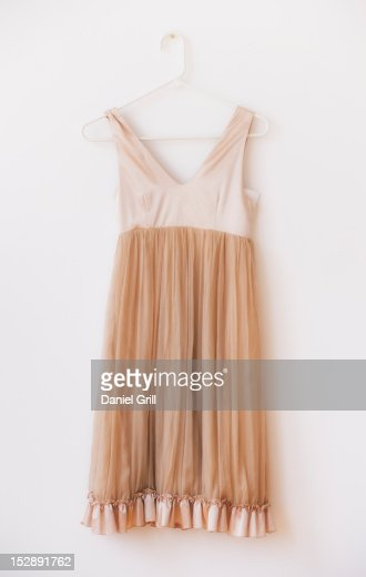 Dress with frill on hanger against white wall