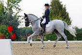 A beautiful young woman riding a Pura Raza Espanola (P.R.E.) horse in dressage test. Canon Eos 1D Mark III.