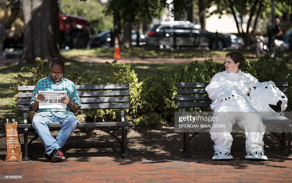 Dressed as a polar bear Megan Gabriel, an activist with the Sierra Club, rests on a bench during a protest in Lafayette Park September 26, 2013 in Washington, DC. Environmental activists gathered to protest the practice of arctic drilling and pressure the Obama administration to do the same. AFP PHOTO/Brendan SMIALOWSKI