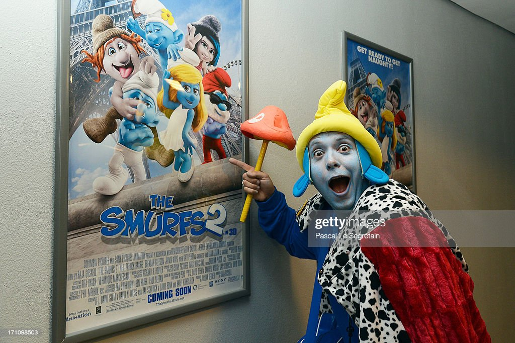 A dressed as a Smurf character poses by a poster of the movie 'The Smurfs 2' as he prepares to board a branded high speed train from Brussels to Paris as part of Global Smurfs Day celebrations on June 22, 2013 at Brussels railway station, Belgium.