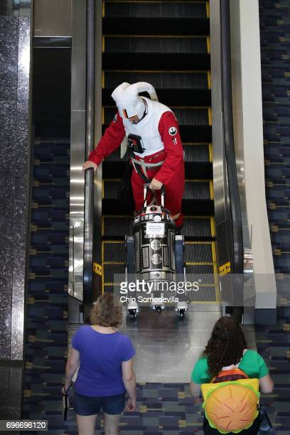 Dressed as a Star Wars Twi'lek pilot Liam Stillman of Purcellville VA wheels his model R2 droid up an escalator during the first day of Awesome Con...