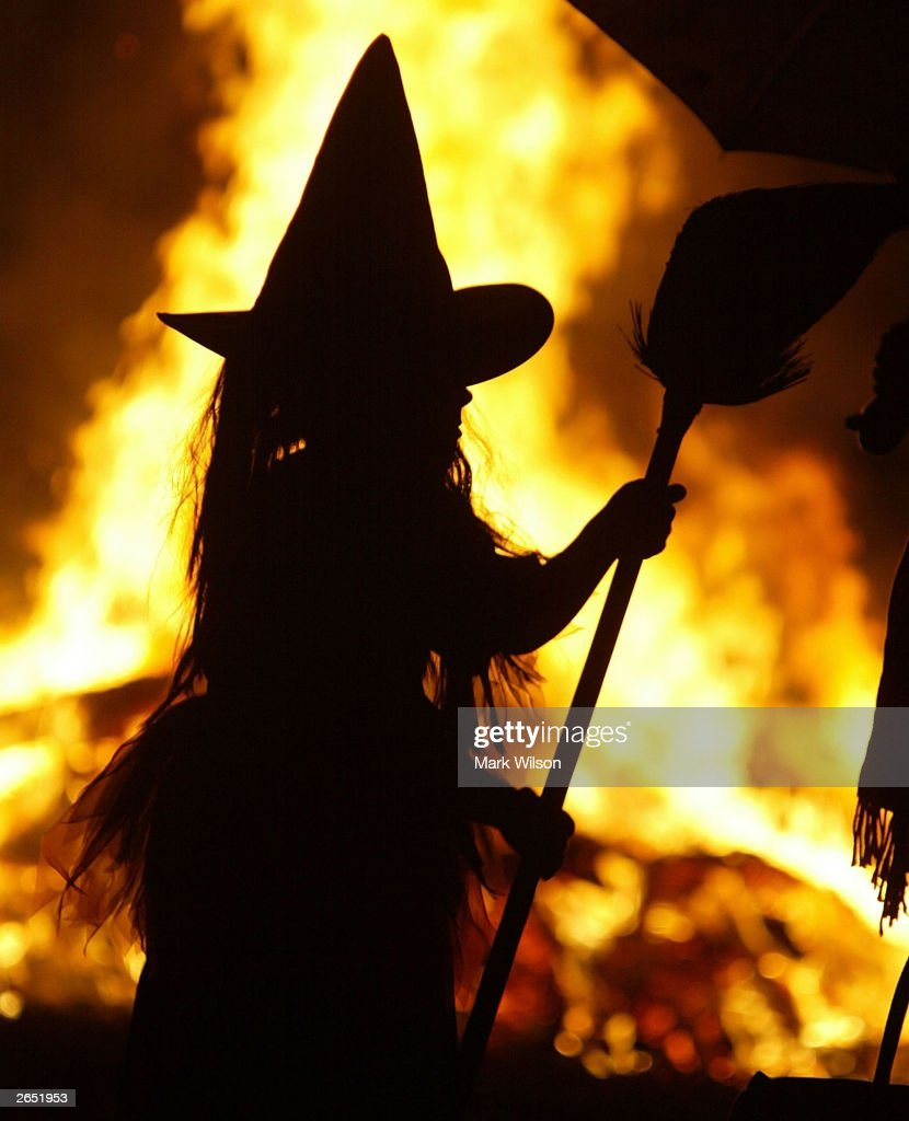 Dressed as a witch Leigh Kosega stands near a bonfire October 25 2003 in Huntingtown Maryland With the sniper suspect arrested parents in the...