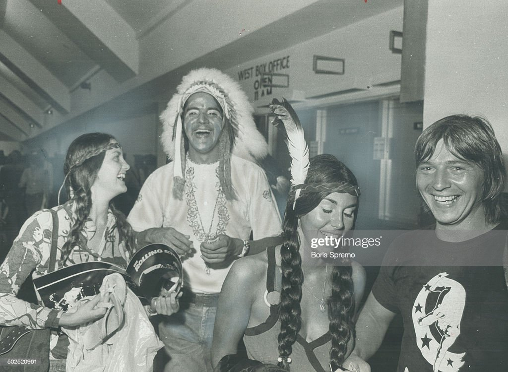Dressed as Indians; three happy fans of the Rolling Stones enjoy the concert in Maple Leaf Gardens. As the temperature and the frenzy mounted in the Gardens; half-naked people stood up and writhed to the frantic music.