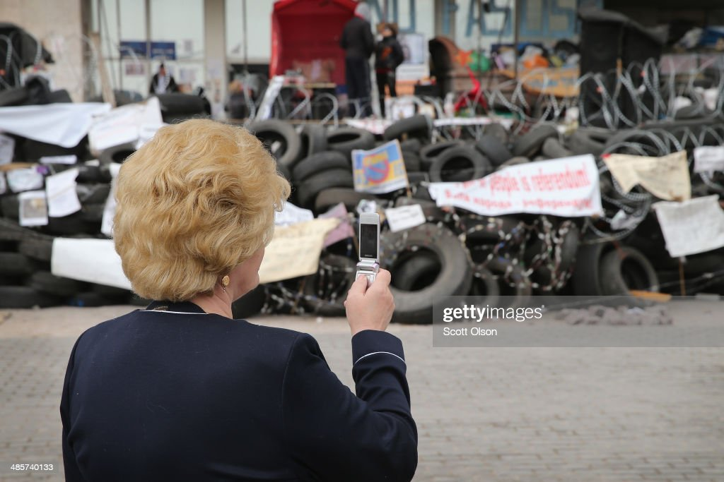 Dressed for Easter service, a woman takes a picture of a barricade which was constructed around the Donetsk Regional Administration building following its recent takeover by pro-Russian activist on April 20, 2014 in Donetsk, Ukraine. The activists who are occupying the building have surrounded it with a barricade of tires and barbed wire and are prepared to defend it with caches of Molotov cocktails strategically placed around the barricade. Activist leader, Denis Pushilin, who is co-head of the self-declared Donetsk People's Republic, said the activists will not surrender until there is a change of leadership in Ukraine. Several bands of separatists, similar to those in Donetsk, have been occupying government buildings in other eastern Ukraine cities in recent weeks