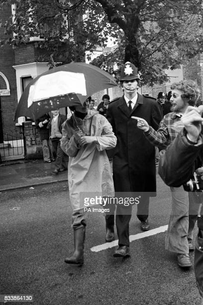 Dressed for the weather under an umbrella a woman picket is led away by police after today's scuffles outside the strike hit factory