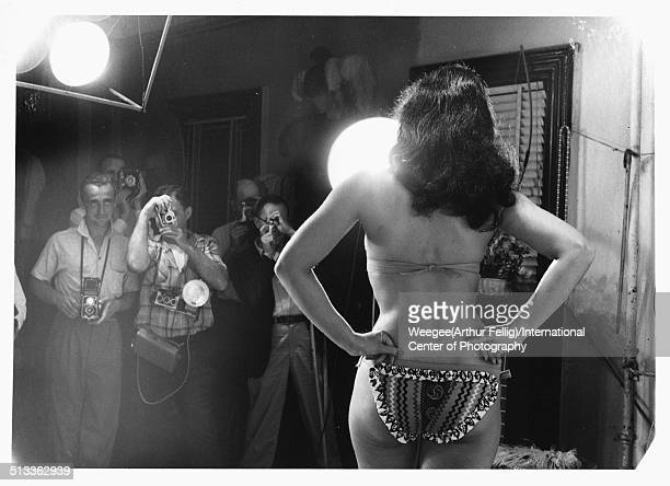 Dressed in a bikini American pinup model Bettie Page poses with her hands on her hips as photographers take her picture 1950s Photo by Weegee...